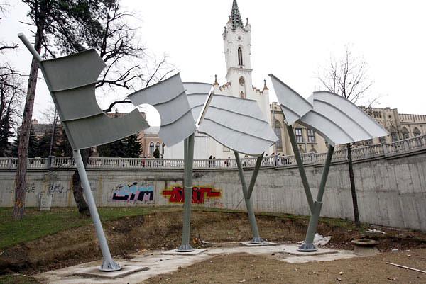A szakma, az építészeti lektorátus is több olyan módosítást javasolt, melyek eredményeként jelentősen megváltozott az emlékmű, például így lett krómacél helyett a hídszürke változat