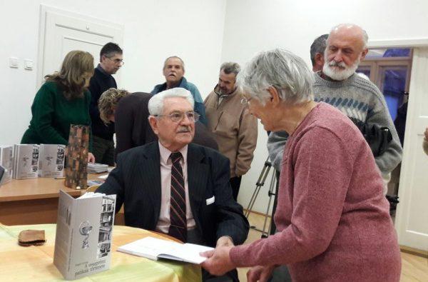 Hogya György huszonharmadik helytörténeti kötetét dedikálja a könyvbemutatón. Fotó: a szerző