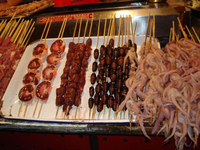 Ínyencségek, köztük lárvák egy pekingi utcai árus kínálatában