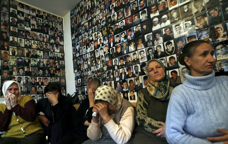 Özvegyek, háttérben az áldozatok fotói. Kép forrása: Magyar Helsinki Bizottság